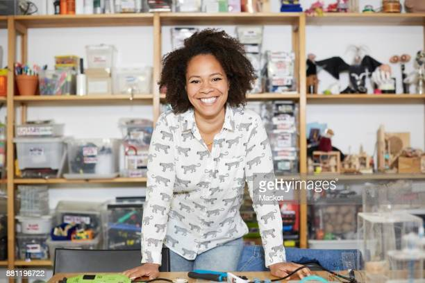 portrait of confident female technician standing against shelf at workshop - inventor stock pictures, royalty-free photos & images