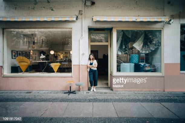 portrait of confident female upholstery worker standing at workshop entrance - front view stock pictures, royalty-free photos & images