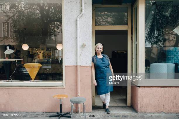 portrait of confident female upholstery worker standing at workshop entrance - schürze stock-fotos und bilder