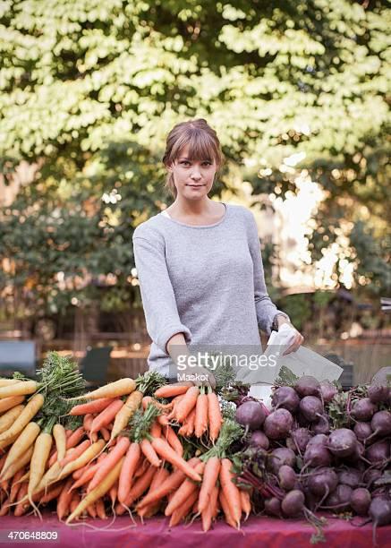 Portrait of confident female vendor selling vegetables at stall