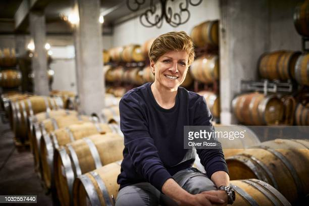 portrait of confident female vintner in wine cellar - viniculture stock pictures, royalty-free photos & images