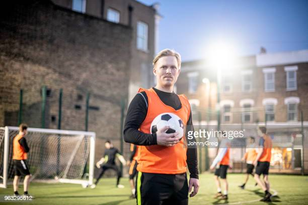 portrait of confident football player in his 30s holding football on pitch at night - amateur stock pictures, royalty-free photos & images