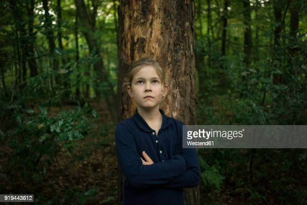 portrait of confident girl standing at tree trunk in forest - alleen één meisje stockfoto's en -beelden
