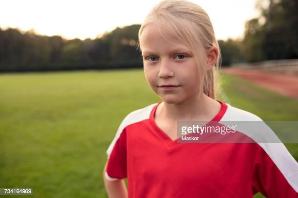 Portrait of confident girl standing on soccer field