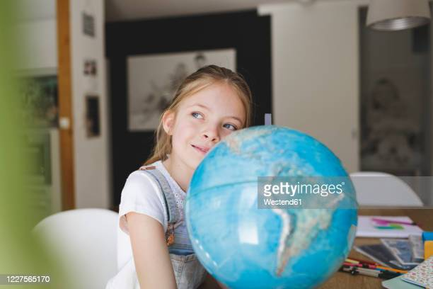 portrait of confident girl with globe at home looking at distance - desiderio foto e immagini stock