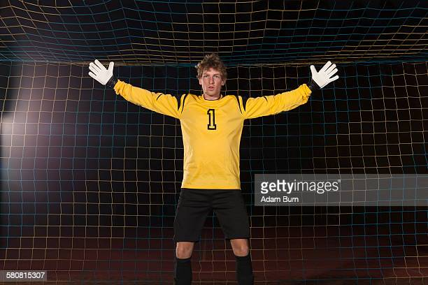 portrait of confident goalie defending soccer net on field - fußballtrikot stock-fotos und bilder