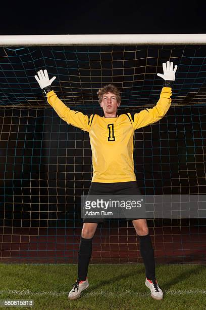 portrait of confident goalie defending soccer net on field - ゴールキーパー ストックフォトと画像