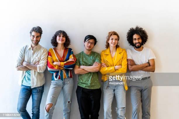 portrait of confident group of friends standing at a wall - photo de groupe photos et images de collection