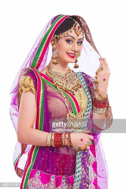Portrait of confident Indian bride smiling against white background