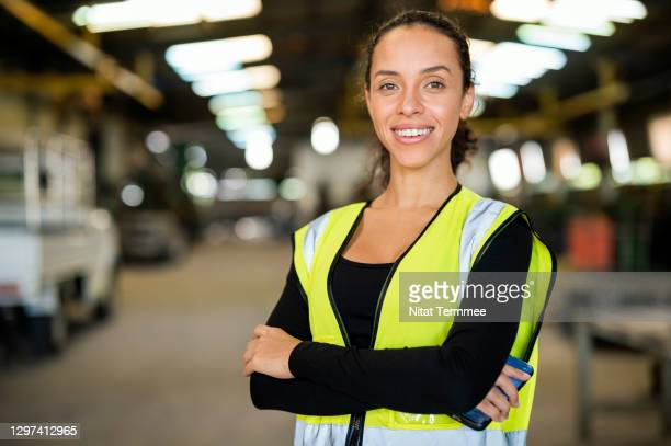 portrait of confident latin female factory manager standing with arm crossed in factory. leadership, quality management, cooperation. - chief executive officer stock pictures, royalty-free photos & images