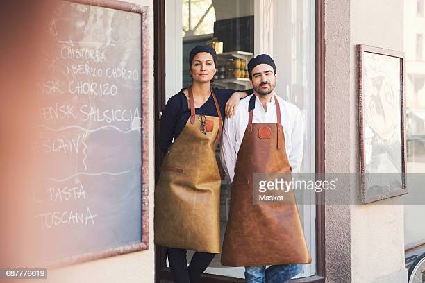Portrait of confident male and female owners standing at grocery store entrance