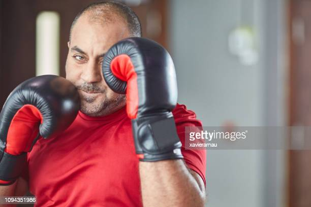 portrait of confident male boxer practicing in gym - martial arts stock pictures, royalty-free photos & images