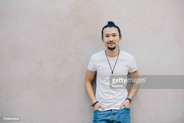 portrait of confident male computer programmer standing with hands in pockets against beige wall in office - man bun stock pictures, royalty-free photos & images