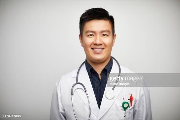 portrait of confident male doctor in lab coat - oost azië stockfoto's en -beelden