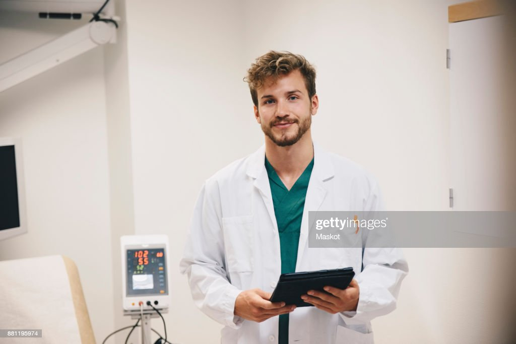 Portrait of confident male doctor standing with digital tablet at hospital : Stock-Foto