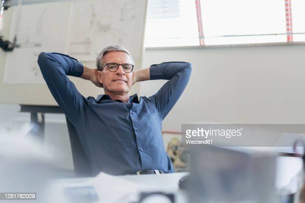 portrait of confident male entrepreneur relaxing while sitting with hands behind head at office desk - hände hinter dem kopf stock-fotos und bilder