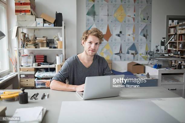 Portrait of confident male fashion designer at laptop in his studio