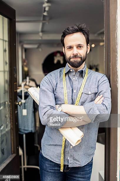 Portrait of confident male fashion designer standing arms crossed at studio doorway