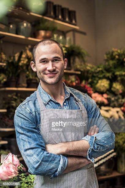 Portrait of confident male florist standing arms crossed at flower shop