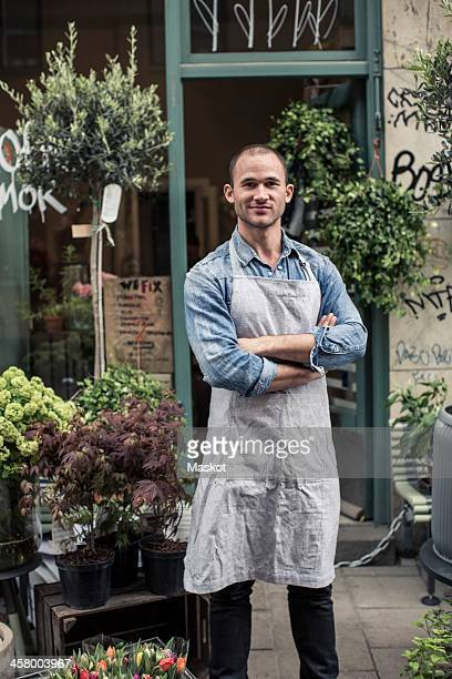 Portrait of confident male florist standing arms crossed outside flower shop