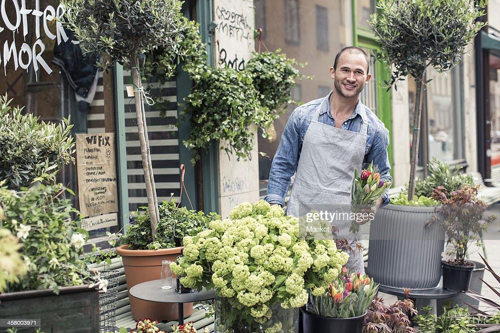 Portrait of confident male florist working outside flower shop : Stock Photo