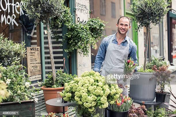 Portrait of confident male florist working outside flower shop