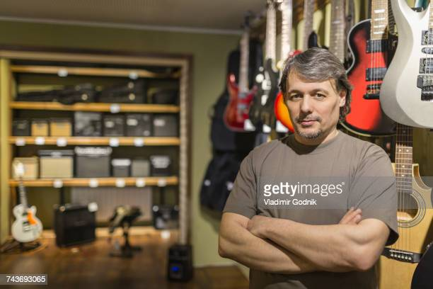 Portrait of confident male owner standing with arms crossed by guitars at store