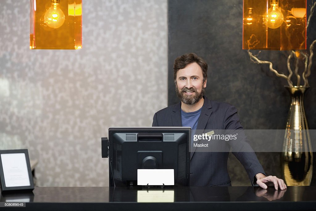 Portrait of confident male receptionist standing at counter in hotel : Foto de stock