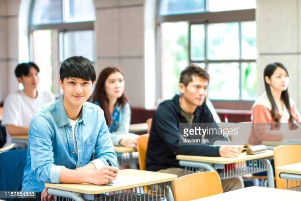 portrait of confident male student sitting in the classroom - ambassador stock pictures, royalty-free photos & images