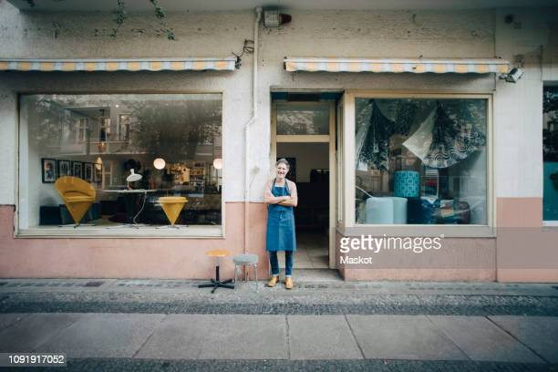 Portrait of confident male upholstery worker standing at workshop entrance