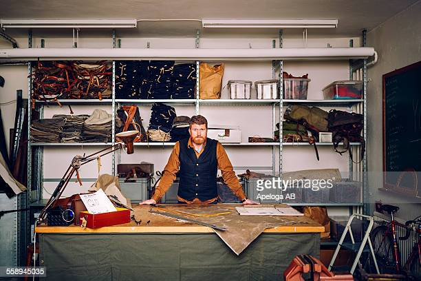 Portrait of confident male worker leaning on worktable in bag factory