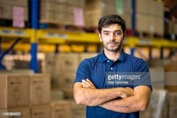 portrait of confident male worker standing with arms crossed while wearing polo uniform in a distribution warehouse. retail, logistic, delivery people. - polo shirt stock pictures, royalty-free photos & images