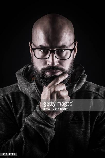 portrait of confident man against black background - completely bald stock photos and pictures