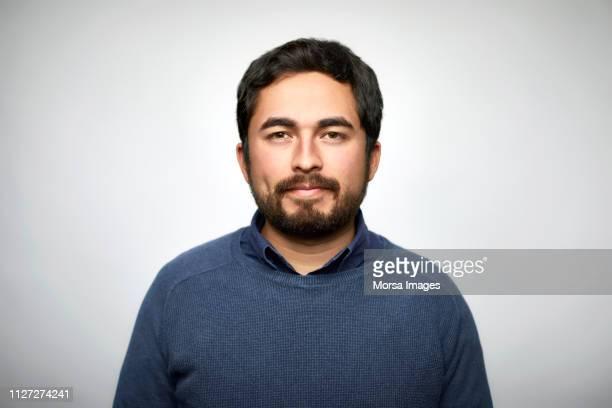 portrait of confident man against white background - latijns amerikaanse en hispanic etniciteiten stockfoto's en -beelden