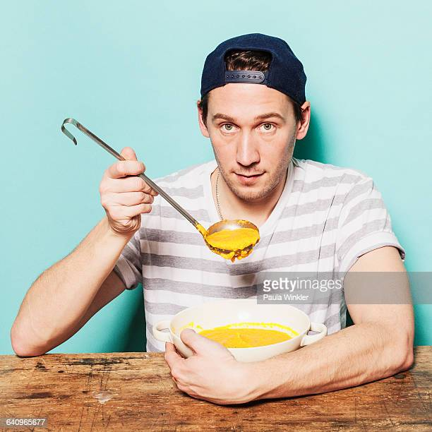 Portrait of confident man having pumpkin soup at table against blue background