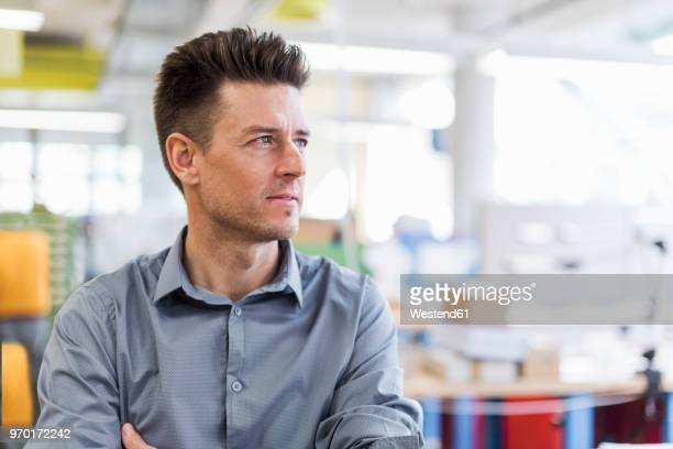 portrait of confident man in factory looking sideways - sideways glance stock pictures, royalty-free photos & images