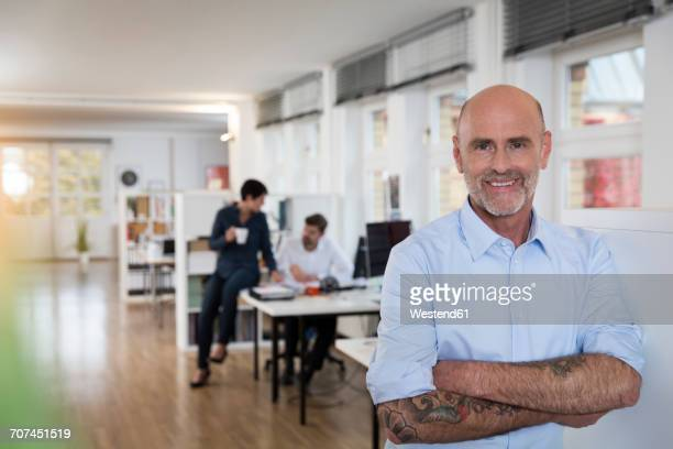 Portrait of confident man in office with colleagues in background
