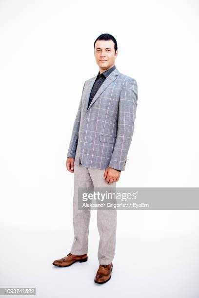 portrait of confident man in suit standing against white background - checked suit stock pictures, royalty-free photos & images