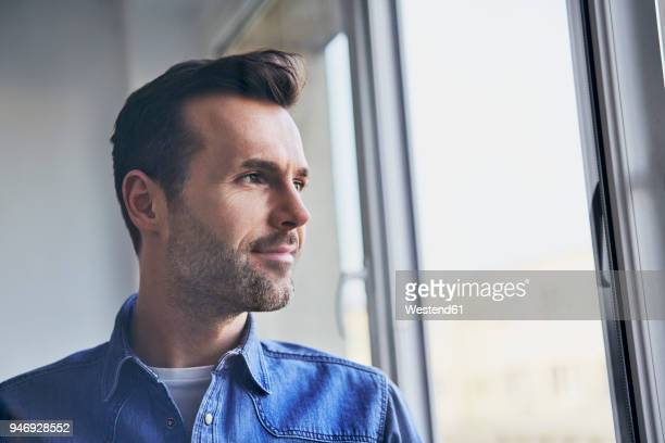 portrait of confident man looking out of window - distrarre lo sguardo foto e immagini stock