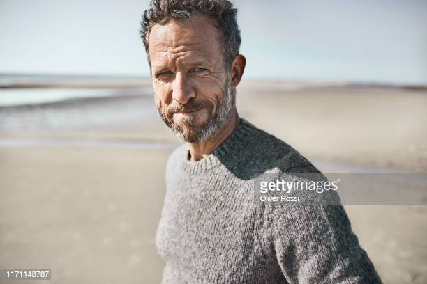 portrait of confident man on the beach - 40 44 jahre stock-fotos und bilder