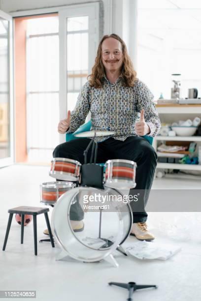 portrait of confident man sitting at toy drums - freizeit stock-fotos und bilder