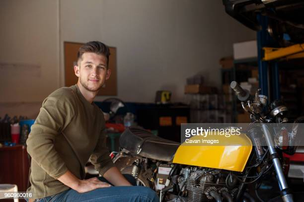 Portrait of confident man sitting by motorcycle in garage