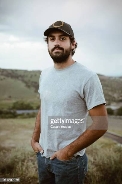 portrait of confident man standing with hands in pockets at field - cap stock pictures, royalty-free photos & images