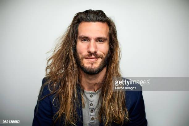 portrait of confident man with long hair - homens imagens e fotografias de stock