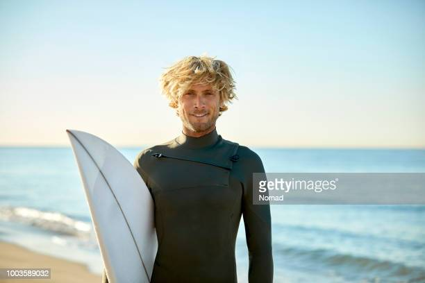 portrait of confident man with surfboard at beach - surf stock pictures, royalty-free photos & images