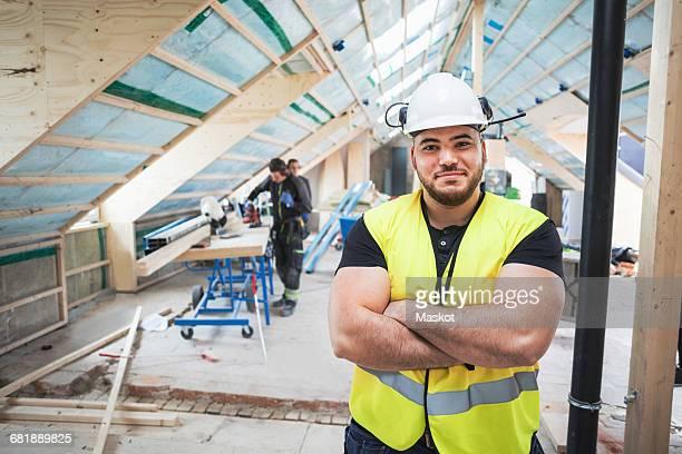 portrait of confident manual worker standing with arms crossed at construction site - bouwvakker stockfoto's en -beelden