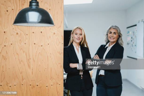 portrait of confident mature and young businesswoman in loft office - 後任 ストックフォトと画像