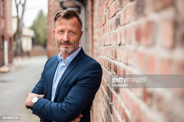 Portrait of confident mature businessman at brick wall