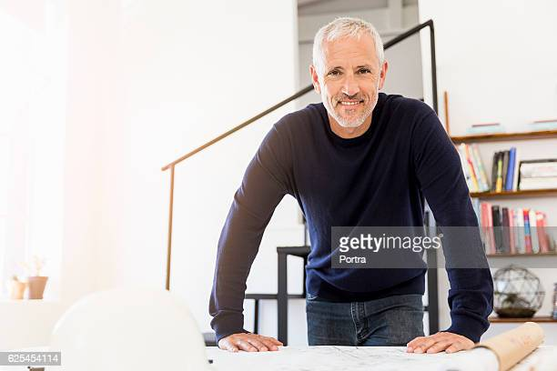 portrait of confident mature businessman at table - leaning stock pictures, royalty-free photos & images