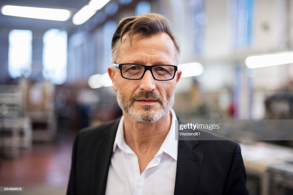Portrait of confident mature businessman in factory : Stock Photo